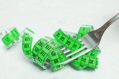 Измеряя лента зеленый цвет, обернутый вокруг штепсельной вилки лежа на wh Стоковое фото RF