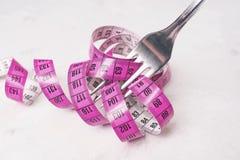 Измеряя лента пинк, обернутый вокруг вилки лежа на whi Стоковое Изображение RF