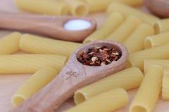 Измеряя ложки с специями и лапшами rigatoni Стоковая Фотография RF
