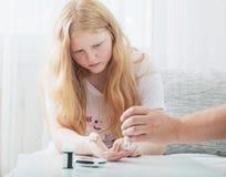 Измеряя уровень сахара в крови предназначенной для подростков девушки Стоковые Изображения