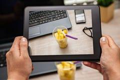 Изображать коробку для завтрака плодоовощ на офисе используя таблетку цифров Стоковая Фотография
