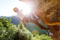 Изображение альпиниста человека в шлеме карабкаясь вверх по скале Стоковое Изображение RF