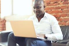 Изображение Афро-американского бизнесмена работая на его компьтер-книжке Красивый молодой человек на его столе Стоковое фото RF