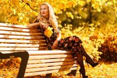 Изображение белокурого усаживания на деревянной скамье в парке осени стоковое изображение