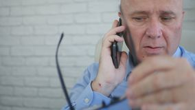 Изображение бизнесмена говоря с чернью и играя с Eyeglasses стоковая фотография rf