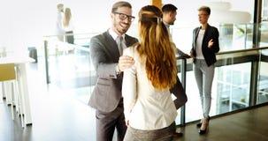 Изображение бизнесмена и коммерсантки говоря в офисе Стоковое Фото