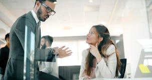 Изображение бизнесмена и коммерсантки говоря в офисе Стоковое Изображение