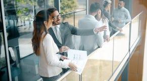 Изображение бизнесмена и коммерсантки говоря в офисе Стоковая Фотография