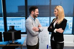 Изображение бизнесмена и коммерсантки говоря в офисе Стоковые Изображения