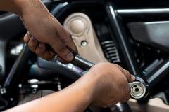 Изображение близкие поднимающие вверх Люди держа руку ремонтируют мотоцикл стоковое фото