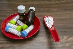Изображение близкого взгляда бутылок вещества гомеопатической медицины в красной плите и таблеток в красной ложке на деревянной п стоковое изображение rf