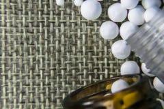 Изображение близкого взгляда гомеопатической медицины состоя из таблеток и бутылок медицины на предпосылке джута стоковая фотография rf