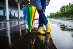 Изображение ботинок и пестрого зонтика молодого бизнесмена желтых в ненастной улице Стоковое фото RF