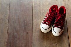 Изображение ботинок ` s девушки на деревянном поле Стоковое Изображение RF