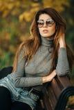 Изображение брюнета в солнечных очках сидя на стенде в парке осени стоковая фотография