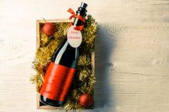 Изображение бутылки вина с карточкой в коробке с сусалью Стоковые Фотографии RF