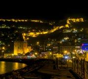 Изображение взгляда ночи старого города около моря с старым замком, домами и пейзажем каменных стен между светами от Alanya Антал Стоковое Фото