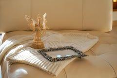Изображение взгляд сверху белого уютного связанного свитера с ангелом и рамки на бежевой кожаной предпосылке софы Уютный свитер р стоковая фотография rf