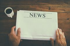 изображение взгляд сверху мужской руки держа пустую газету с пустым космосом для того чтобы добавить новости или текст тип повели стоковая фотография rf