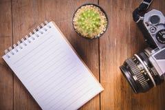 изображение взгляд сверху открытой тетради с пустыми страницами и кактусом и камеры на деревянном столе Стоковые Изображения