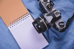 изображение взгляд сверху открытой тетради с пустыми страницами и кактусом и камеры на деревянном столе Стоковая Фотография