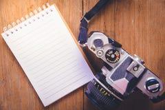 Изображение взгляд сверху открытой тетради с пустыми страницами и камеры на деревянном столе Стоковое Изображение RF