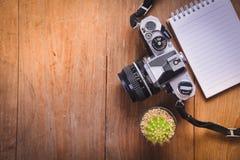 изображение взгляд сверху открытой тетради с пустыми страницами и кактусом и камеры на деревянном столе Стоковое фото RF
