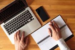 Изображение взгляд сверху рук бизнесмена с компьтер-книжкой Стоковое Изображение