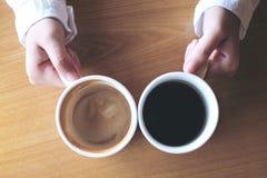 Изображение взгляд сверху рук держа 2 белых чашки кофе на древесине Стоковое фото RF