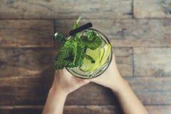Изображение взгляд сверху рук держа стекло замороженного лимонного сока с листьями мяты на деревянном столе Стоковое фото RF