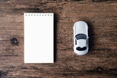 Изображение взгляд сверху тетради пустой страницы и малый автомобиль моделируют на Стоковое Фото