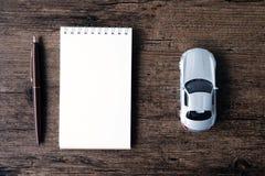 Изображение взгляд сверху тетради пустой страницы, ручка и малый автомобиль моделируют o Стоковое Фото