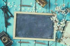 Изображение взгляд сверху дерева вишневых цветов весны белого, классн классного, старой камеры на голубом деревянном столе Стоковые Изображения RF