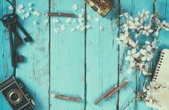 Изображение взгляд сверху дерева вишневых цветов весны белого, пустой тетради, старой камеры на голубом деревянном столе тонизиро Стоковая Фотография RF