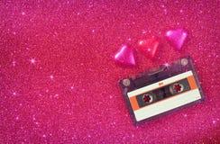 Изображение взгляд сверху красочных шоколадов и магнитофонной кассеты формы сердца на розовой предпосылке яркого блеска Стоковое Фото