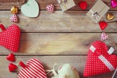 Изображение взгляд сверху красочных шоколадов формы сердца, сердец ткани и подарочных коробок на деревянном столе Стоковые Фотографии RF