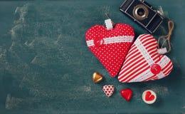 Изображение взгляд сверху красочных шоколадов формы сердца, сердца ткани и камеры фото года сбора винограда на предпосылке доски Стоковые Изображения RF