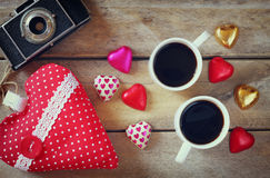Изображение взгляд сверху красочных шоколадов формы сердца, сердца ткани, винтажной камеры фото и чашки кофе на деревянном столе Стоковые Фото