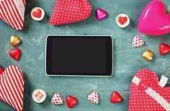 Изображение взгляд сверху таблетки, красочных шоколадов формы сердца, сердец ткани на предпосылке классн классного Стоковое фото RF