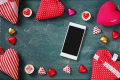 Изображение взгляд сверху smartphone, красочных шоколадов формы сердца, сердец ткани на предпосылке классн классного Стоковое Изображение RF