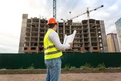 Изображение вид сзади мужского архитектора в красном защитном шлеме держа светокопии и смотря здание под конструкцией Стоковое Изображение