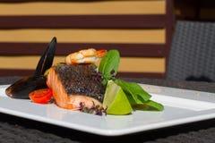 Изображение вкусных испеченных семг с креветкой и устрицей на блюде Стоковая Фотография