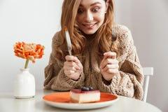 Изображение голодной женщины сидя на таблице, и есть торт с app Стоковые Фото