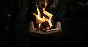 Изображение горения книги в руках женщины в лесе Стоковая Фотография