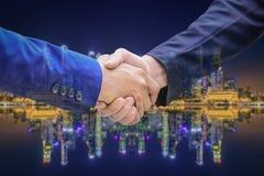 Изображение двойной экспозиции рукопожатия бизнесмена на nightli города Стоковое фото RF