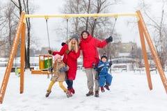 Изображение девушки и мальчика отбрасывая в зиме в парке с родителями Стоковая Фотография RF