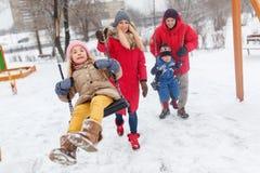 Изображение девушки и мальчика отбрасывая в зиме в парке с родителями Стоковые Изображения RF