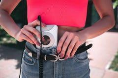 Изображение девушки кладя аудиоплейер в джинсы задыхается Аудиоплейер бел и соединен к наушникам шнуром Стоковое фото RF
