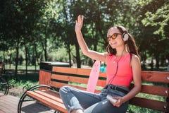 Изображение девушки сидя на стенде и развевать Она держит аудиоплейер в ее руках и слушает к музыке до конца Стоковое фото RF
