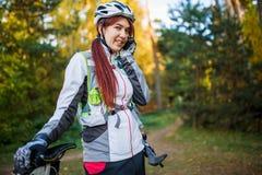 Изображение девушки с велосипедом в шлеме говоря на телефоне Стоковые Фото